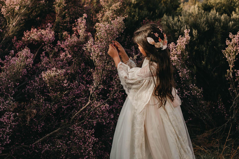 Fotografía de una niña con un vestido de comunión recogiendo flores del brezo