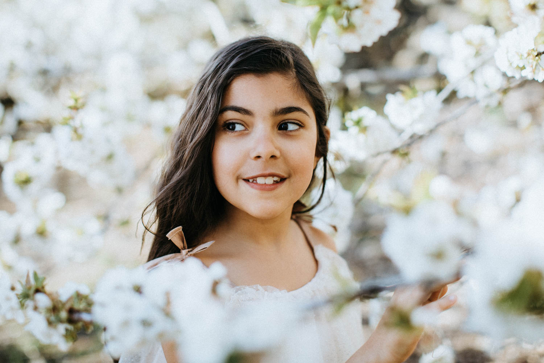 Retrato de una niña de comunión entre flores de cerezos