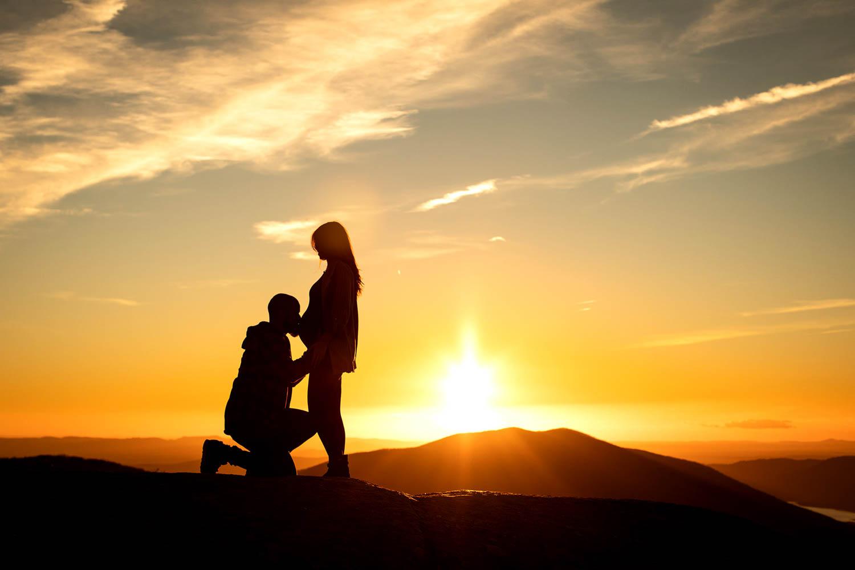 Pareja en una puesta de sol, él besando la barriguita de su chica embarazada