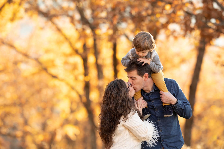 Pareja se besa con su hijo a hombros en un bosque en otoño -Sesión Lifestyle