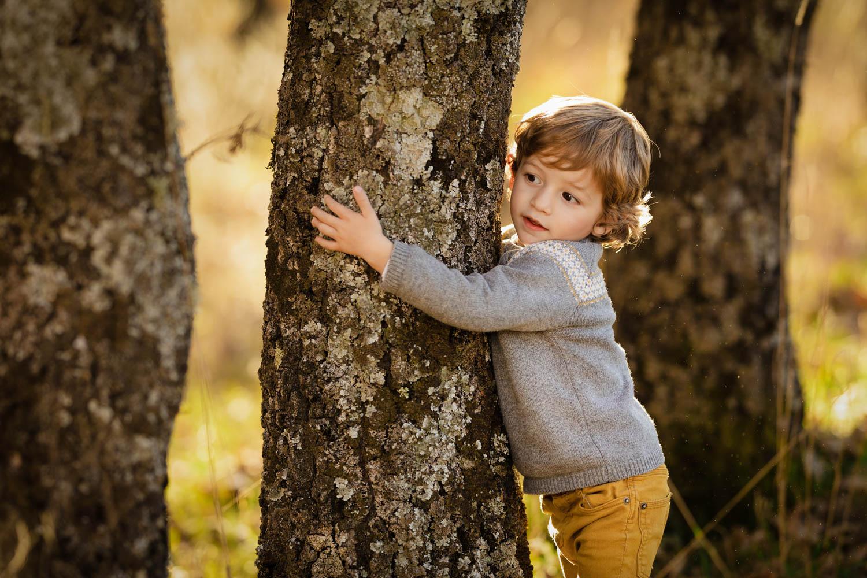 Niño juega entre los árboles al atardecer