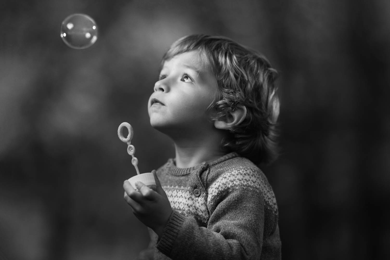 Niño jugando con una pompa de jabón en el campo en otoño - Fotografía blanco y negro